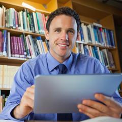Handsome librarian sitting at desk using tablet