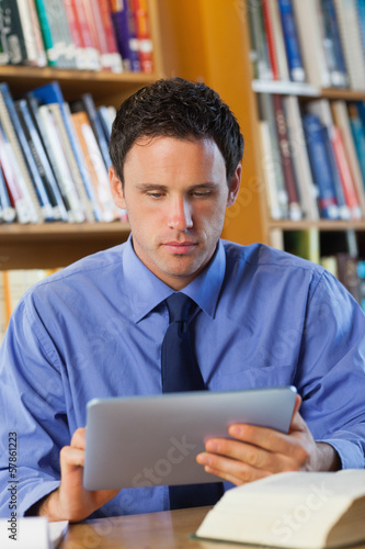Calm librarian sitting at desk using tablet