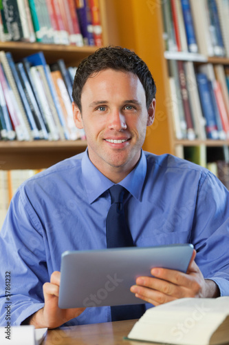 Smiling librarian sitting at desk using tablet