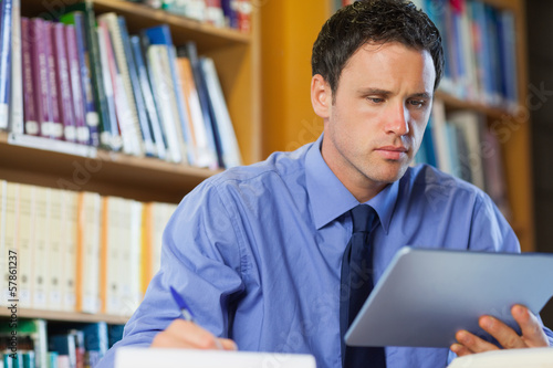 Frowning librarian sitting at desk using tablet