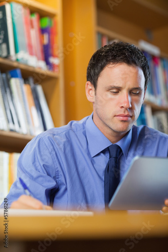 Focused librarian sitting at desk using tablet