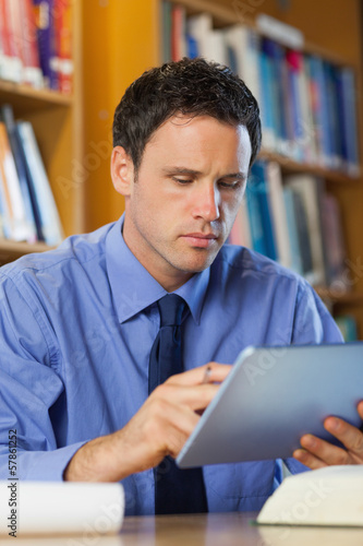 Concentrating librarian sitting at desk using tablet