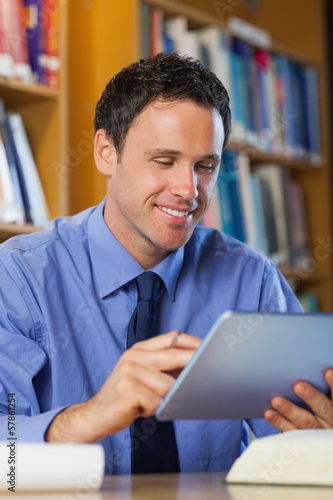 Cheerful librarian sitting at desk using tablet