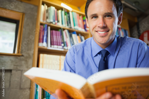 Cheerful librarian sitting at desk reading a book