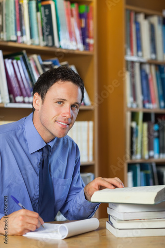 Smiling librarian sitting at desk taking notes