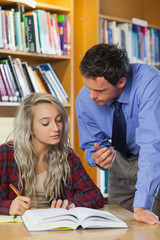 Lecturer explaining something to blonde serious student
