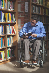 Focused man in wheelchair reading a book