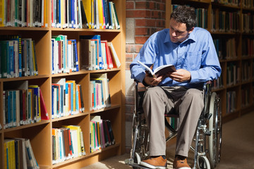 Serious man in wheelchair reading a book
