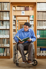 Calm man in wheelchair reading a book