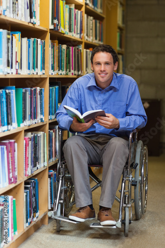 Happy man in wheelchair holding a book