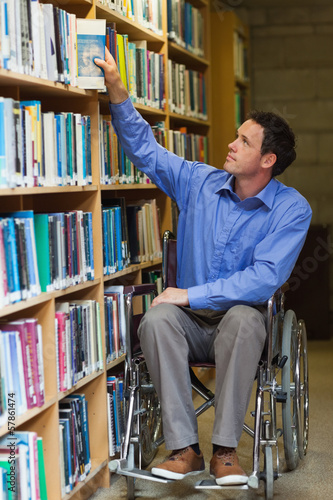 Calm man in wheelchair taking a book out of bookshelf