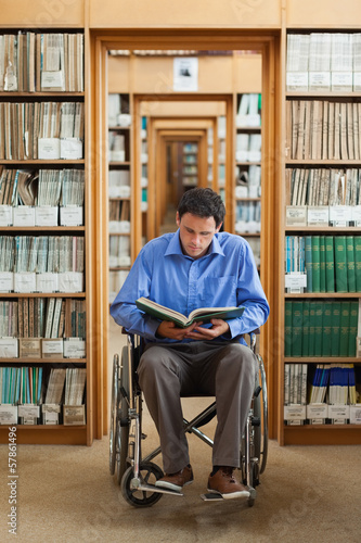 Attractive man in wheelchair reading a book