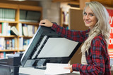 Pretty blonde student using photocopier