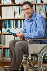 Smiling man sitting in wheelchair holding a book