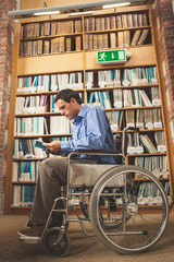 Frowning man sitting in wheelchair reading a book