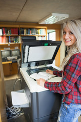 Smiling blonde student using photocopier