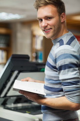 Smiling handsome student standing in front of photocopier