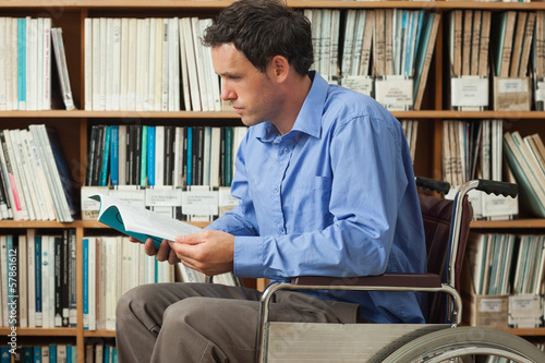 Serious man sitting in wheelchair reading a book