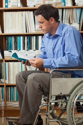 Concentrating man sitting in wheelchair reading a book