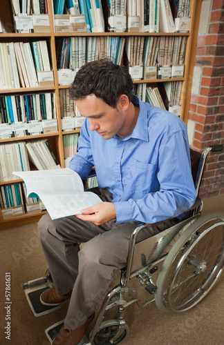 Calm man sitting in wheelchair reading a book