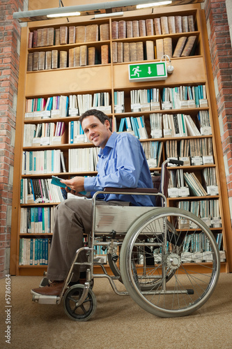 Cheerful man sitting in wheelchair holding a book