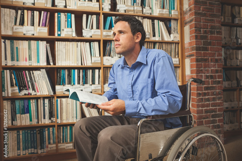 Thoughtful man sitting in wheelchair holding a book