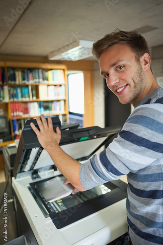 Smiling handsome student using photocopier