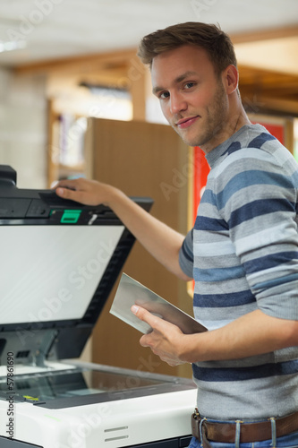 Happy handsome student using photocopier