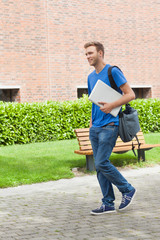 Happy handsome student carrying laptop