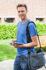 Happy handsome student holding tablet