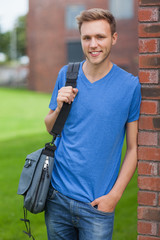 Happy handsome student leaning against wall