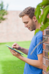 Happy handsome student leaning against wall using tablet