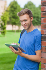 Cheerful handsome student leaning against wall holding tablet