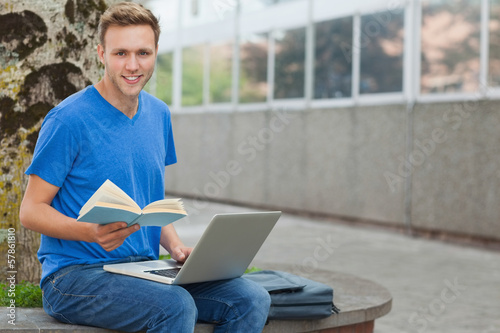 Happy handsome student sitting on wall studying