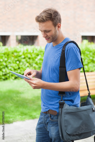 Happy handsome student using tablet
