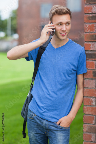 Happy handsome student leaning against wall phoning