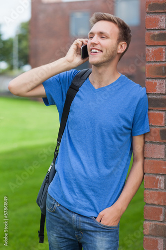 Cheerful handsome student leaning against wall phoning