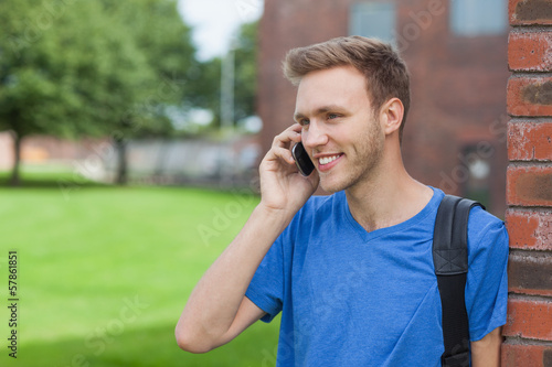 Smiling handsome student leaning against wall phoning