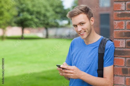 Cheerful handsome student leaning against wall texting