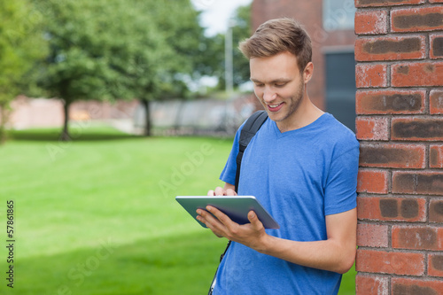 Smiling handsome student leaning against wall using tablet
