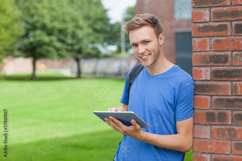 Cheerful handsome student leaning against wall using tablet