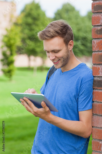Content handsome student leaning against wall using tablet