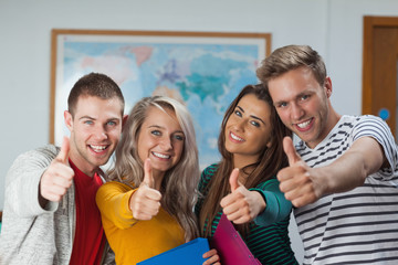 Cheerful casual students showing thumbs up