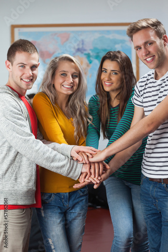Cheerful casual students holding hands together