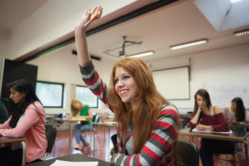Smiling female student raising her hand in class