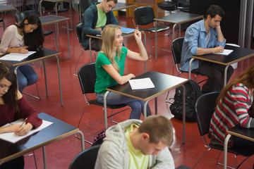 Blonde student raising her hand in class