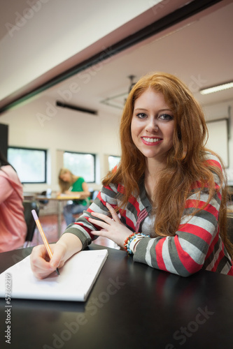 Happy female student looking at camera in class