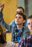 Focused student raising his hand in lecture