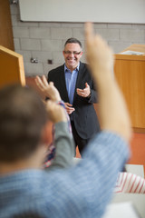 Happy lecturer pointing at student raising his hand