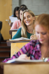Pretty blonde student smiling at camera in a lecture hall